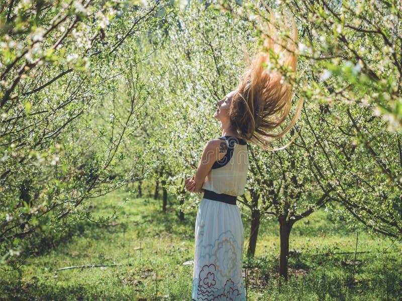 Mujer hermosa joven con el pelo rubio largo del vuelo en árboles del flor de la primavera imagen de archivo libre de regalías