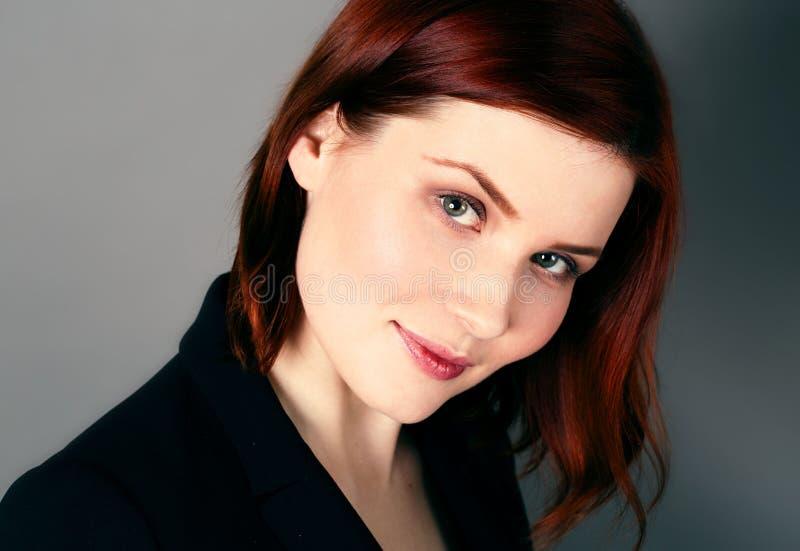 Mujer hermosa joven con el retrato rojo del pelo y de la sonrisa en fondo gris oscuro foto de archivo