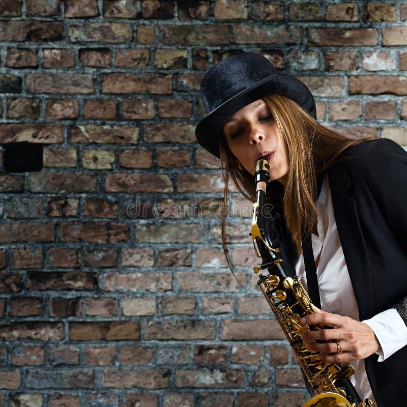 Mujer hermosa joven con el saxofón foto de archivo