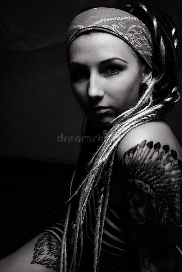 Mujer hermosa joven con el tatuaje y los dreadlocks foto de archivo