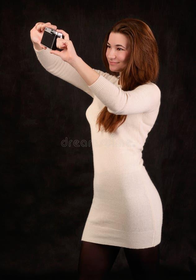 Mujer hermosa joven que toma una imagen de sí misma foto de archivo