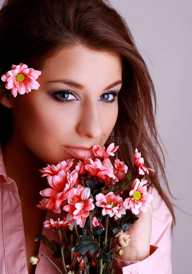 Mujer hermosa joven con la flor rosada fotos de archivo