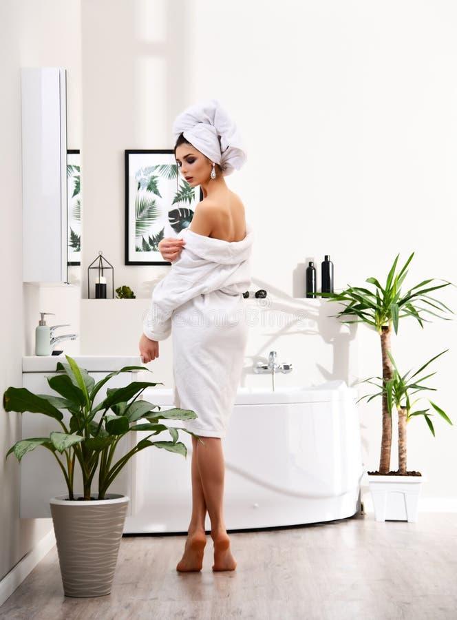 Mujer hermosa joven con la toalla blanca en la cabeza que coloca la albornoz que lleva de la bañera cercana en cuarto de baño mod foto de archivo