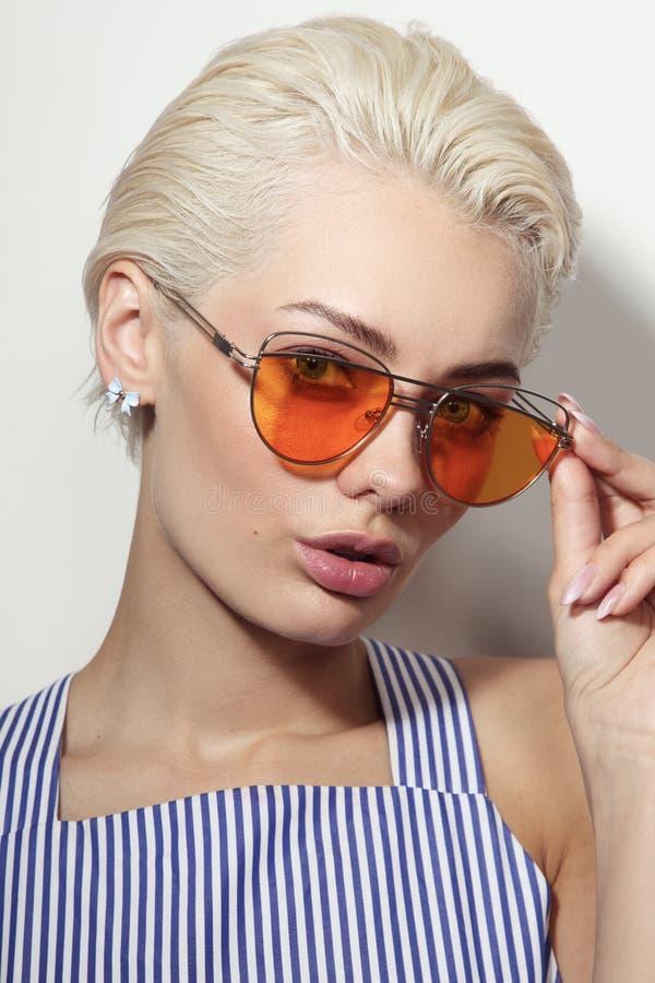 Mujer hermosa joven con las gafas de sol elegantes fotografía de archivo
