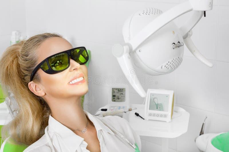 Mujer hermosa joven con los dientes blancos hermosos que se sientan en una silla dental imágenes de archivo libres de regalías