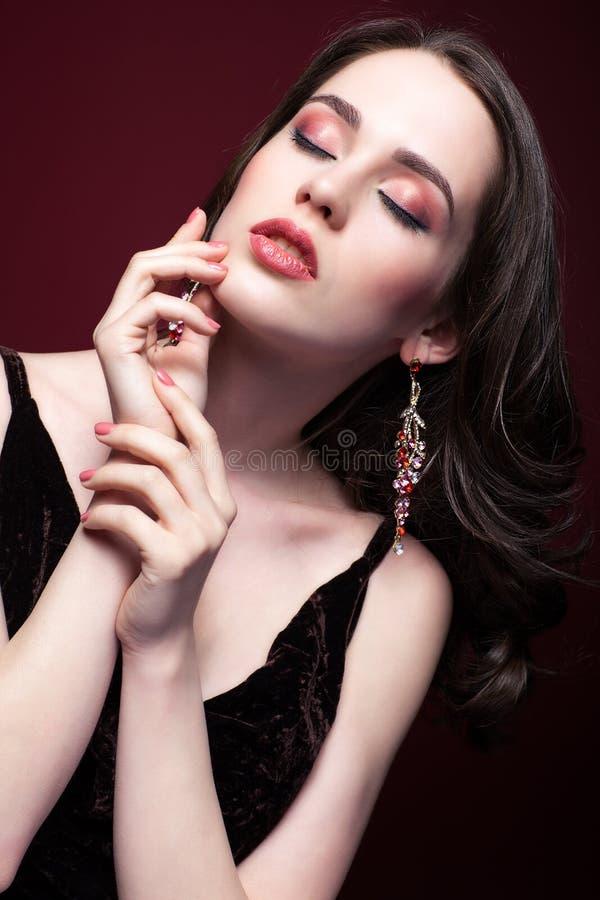 Mujer hermosa joven con los ojos cerrados en fondo rojo del marsala fotografía de archivo