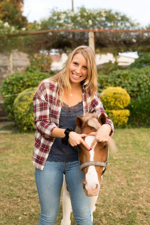 Mujer hermosa joven con un caballo fotos de archivo libres de regalías