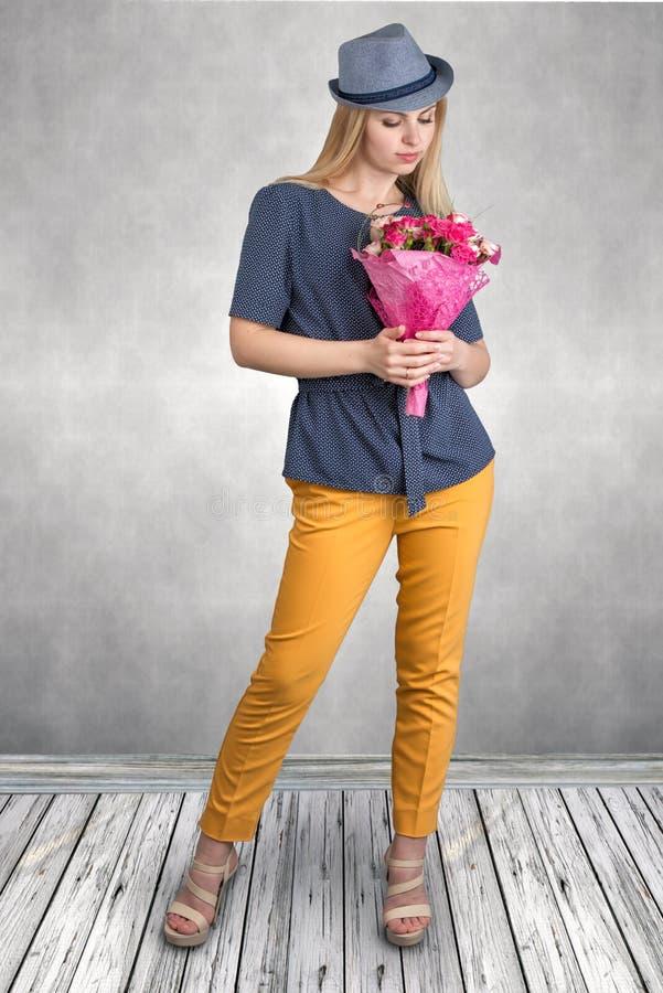 Mujer hermosa joven con un ramo de rosas fotografía de archivo