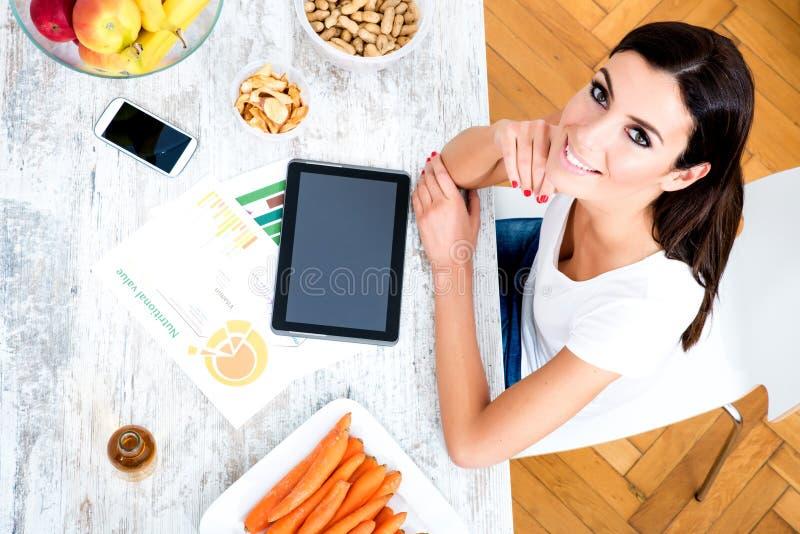 Mujer hermosa joven con un Tablet PC en casa imagen de archivo