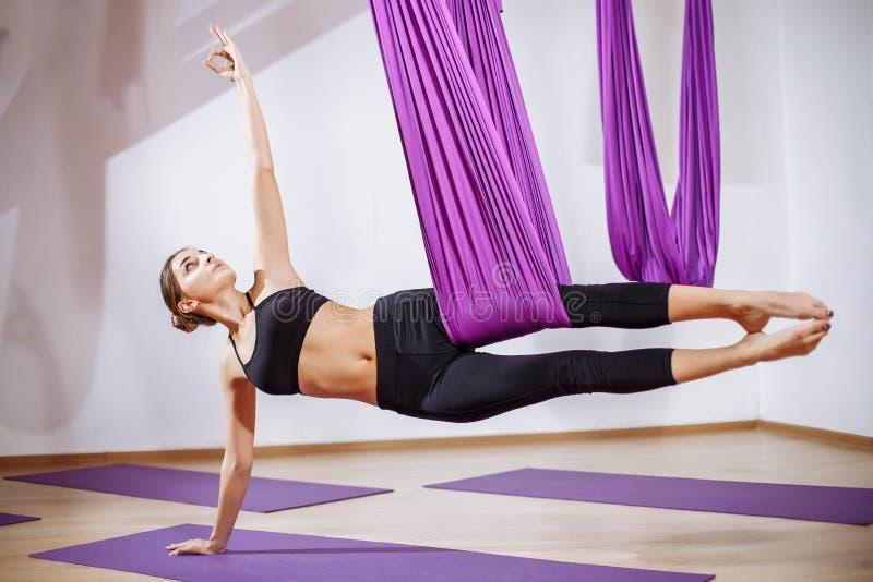 Mujer hermosa joven de la yogui que hace práctica aérea de la yoga en hamaca púrpura en club de fitness imagen de archivo libre de regalías