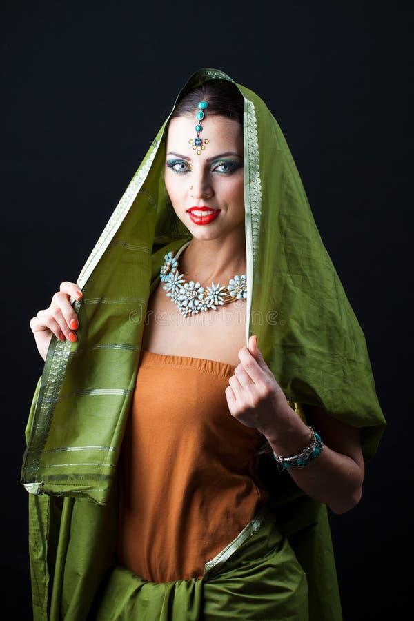Mujer hermosa joven del bruenette en sari verde imagen de archivo