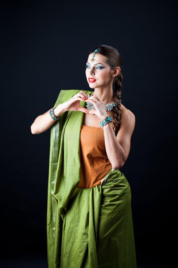 Mujer hermosa joven del bruenette en sari verde fotos de archivo