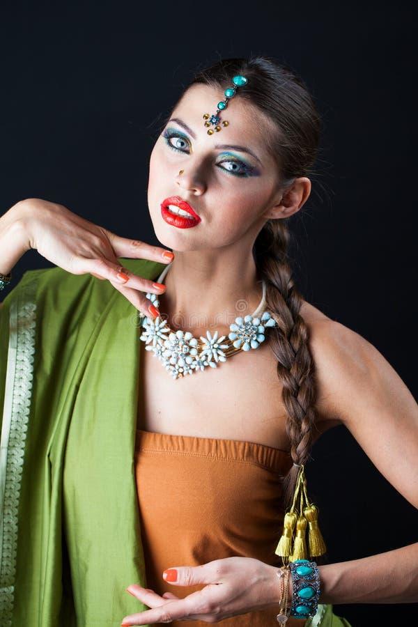 Mujer hermosa joven del bruenette en sari verde imagen de archivo libre de regalías