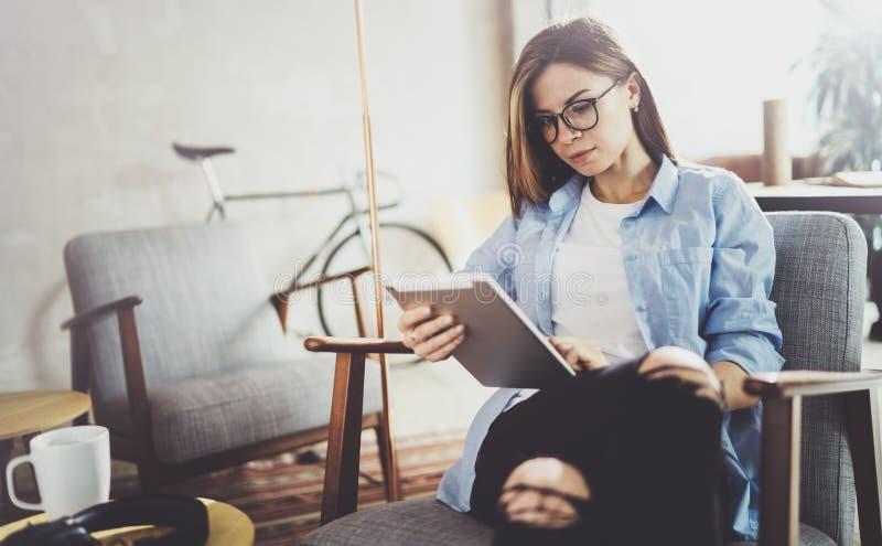 Mujer hermosa joven del inconformista que hojea con el dispositivo de la pantalla táctil en el lugar de trabajo coworking moderno imagen de archivo