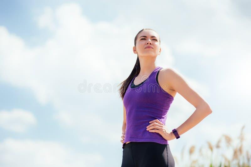 Mujer hermosa joven deportiva permanente antes o después del entrenamiento y del funcionamiento Centrado en ejercicios en fondo d imagen de archivo