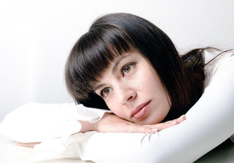 Mujer hermosa joven detrás del pensamiento del escritorio imagen de archivo libre de regalías