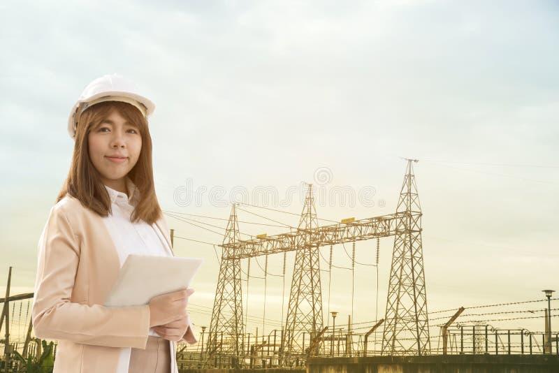 Mujer hermosa joven elegante del ingeniero eléctrico que trabaja usando la tableta para comprobar las redes eléctricas en la fábr foto de archivo
