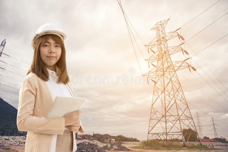 Mujer hermosa joven elegante del ingeniero el?ctrico que trabaja usando la tableta para comprobar las redes el?ctricas en la f?br fotografía de archivo libre de regalías