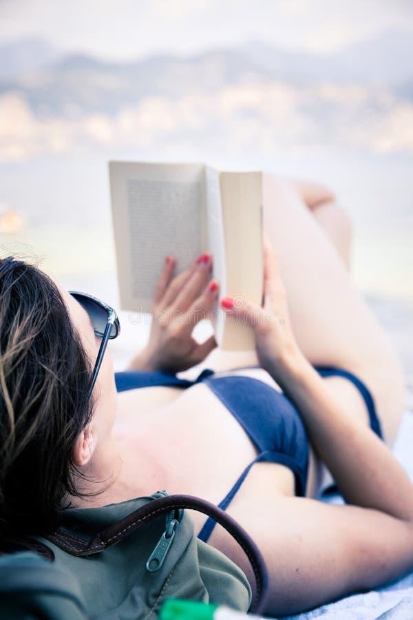 Mujer hermosa joven en bikini que lee un libro en la playa imagen de archivo