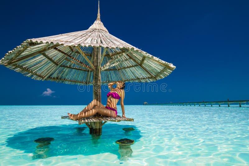 Mujer hermosa joven en bikinis debajo del parasol de playa en el oce fotografía de archivo libre de regalías
