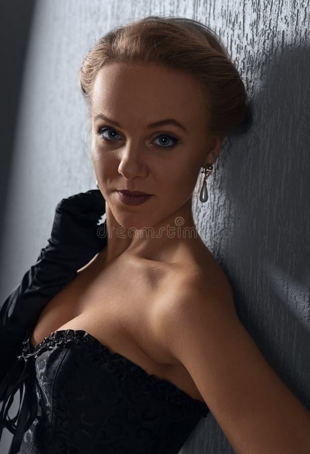 Mujer hermosa joven en corsé negro con los pendientes de la perla foto de archivo libre de regalías