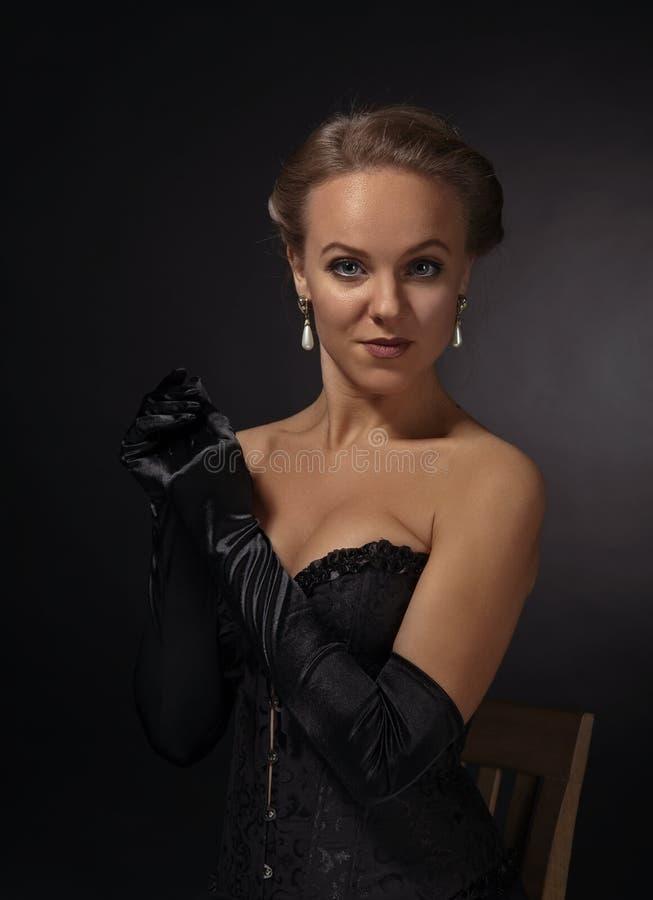 Mujer hermosa joven en corsé negro con los pendientes de la perla fotografía de archivo libre de regalías