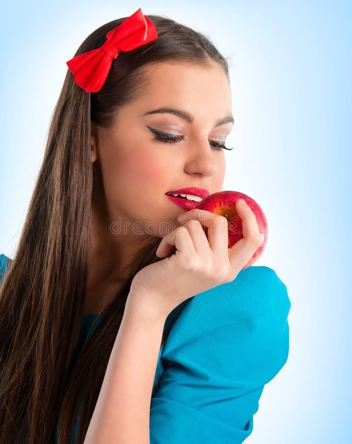 Mujer hermosa joven en el azul que sostiene una manzana fotos de archivo libres de regalías