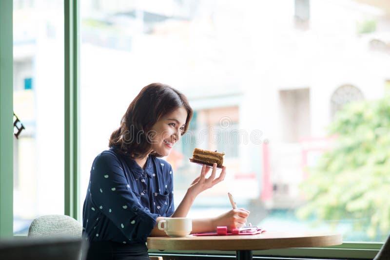 Mujer hermosa joven en el café cerca de la ventana, pensando y foto de archivo