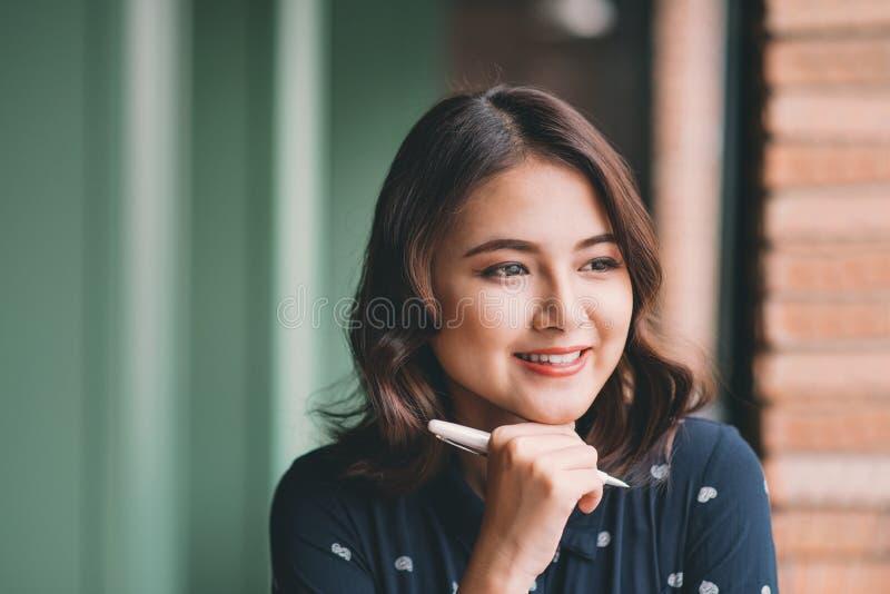 Mujer hermosa joven en el café cerca de la ventana, pensando y escribiendo algo fotos de archivo