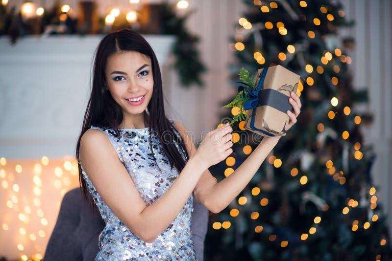 Mujer hermosa joven en el vestido de noche elegante azul que se sienta en piso cerca del árbol de navidad y presentes en una Noch fotos de archivo