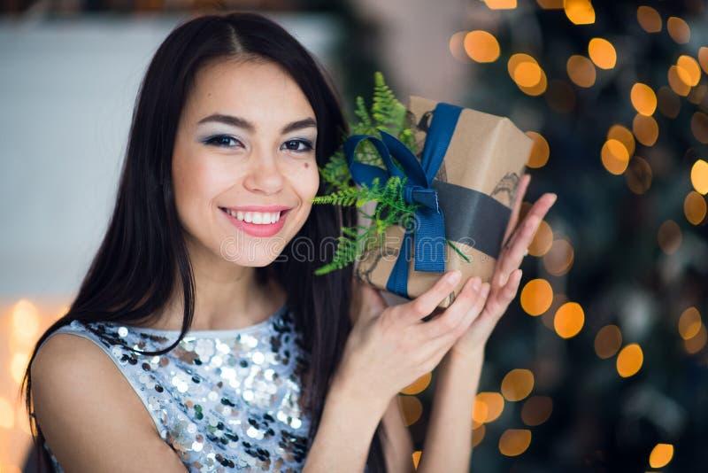 Mujer hermosa joven en el vestido de noche elegante azul que se sienta en piso cerca del árbol de navidad y presentes en una Noch foto de archivo libre de regalías