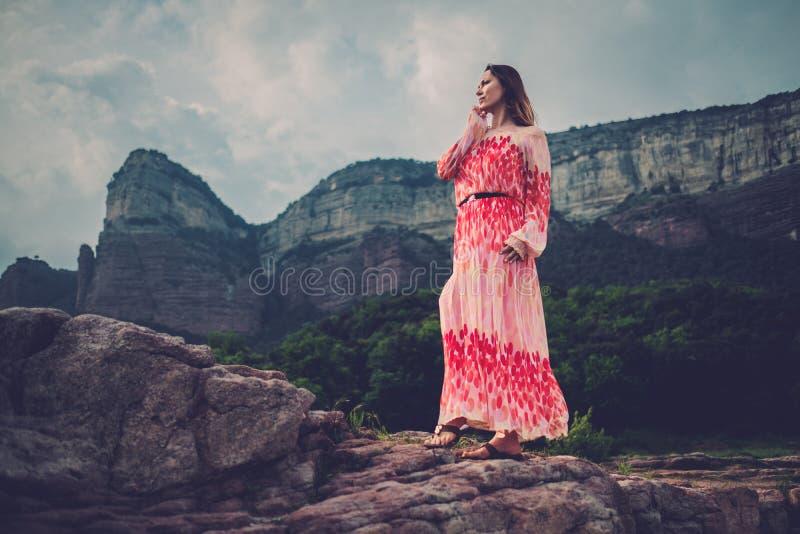 Mujer hermosa joven en el vestido rojo que mira en las montañas España, Sant Roma de Sau imágenes de archivo libres de regalías