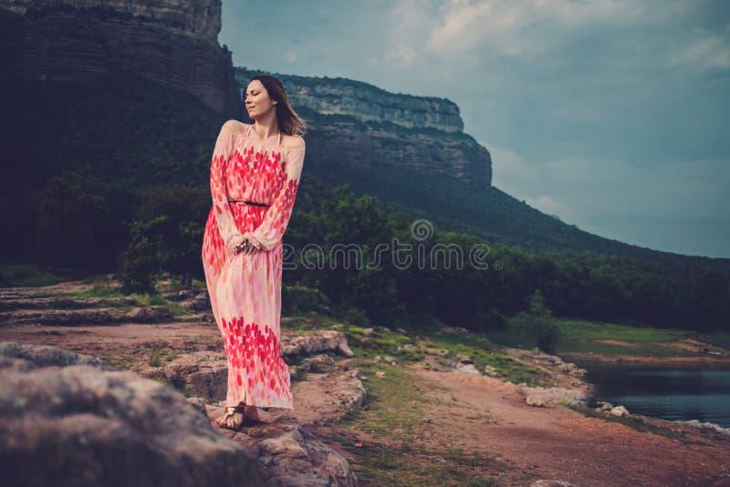 Mujer hermosa joven en el vestido rojo que mira en las montañas España, Sant Roma de Sau imagen de archivo