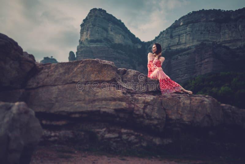 Mujer hermosa joven en el vestido rojo que mira en las montañas España, Sant Roma de Sau fotos de archivo