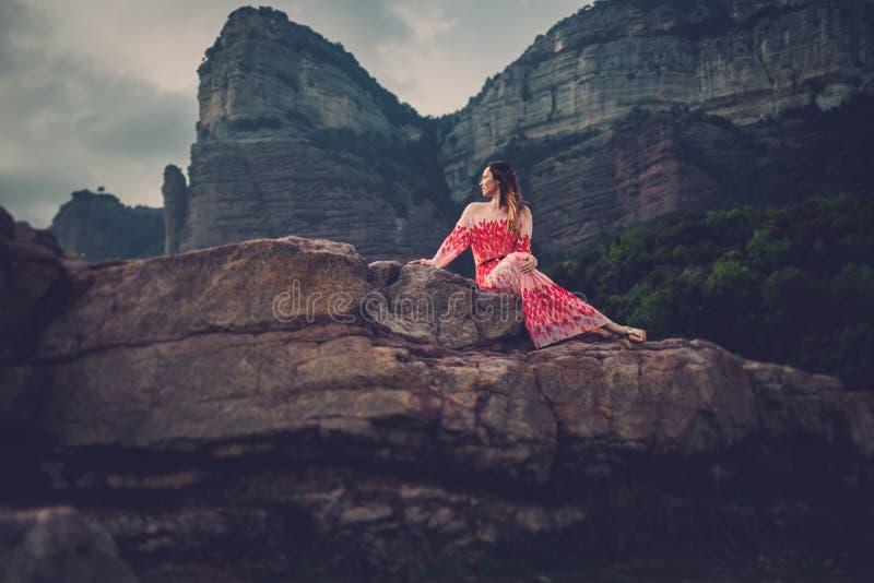 Mujer hermosa joven en el vestido rojo que mira en las montañas España, Sant Roma de Sau foto de archivo libre de regalías