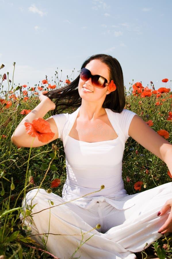 Mujer hermosa joven en flores de la amapola imagen de archivo libre de regalías