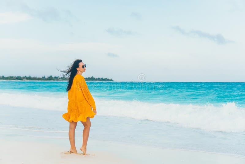 Mujer hermosa joven en la costa tropical en puesta del sol fotos de archivo
