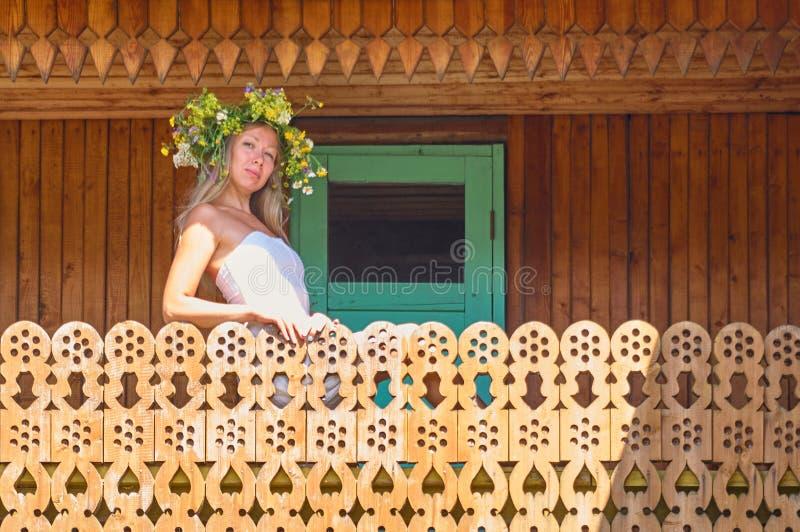 Mujer hermosa joven en la estancia blanca de la guirnalda del vestido y de la flor en el balcón decorativo de la casa del campo e imagenes de archivo