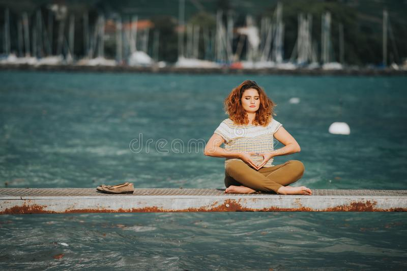 Mujer hermosa joven en la posición de loto que reflexiona sobre el lago fotografía de archivo libre de regalías