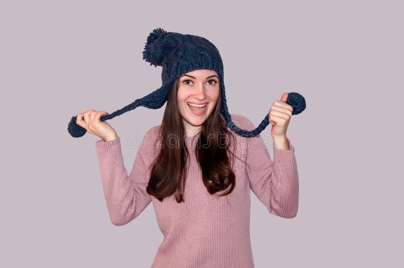 Mujer hermosa joven en suéter y sombrero hecho punto divertido en Grey Background Concepto del invierno foto de archivo libre de regalías