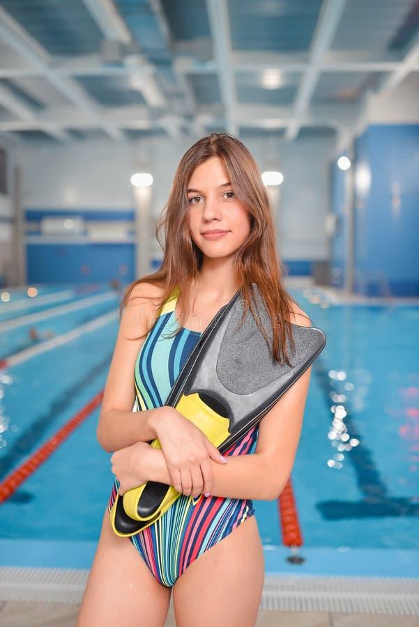 Mujer hermosa joven en traje de baño con las aletas que presentan en el área de la piscina foto de archivo libre de regalías