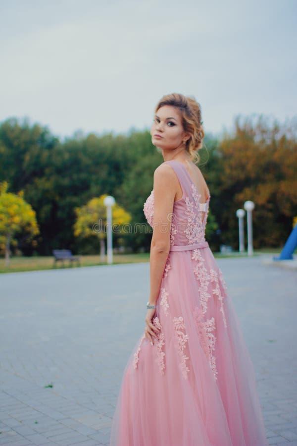 Mujer hermosa joven en trayectoria que camina rosada larga del vestido de noche en parque Forme el retrato del estilo de la mucha foto de archivo