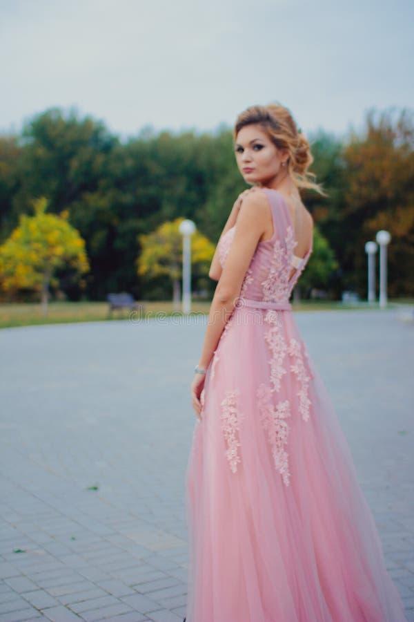Mujer hermosa joven en trayectoria que camina rosada larga del vestido de noche en parque Forme el retrato del estilo de la mucha foto de archivo libre de regalías
