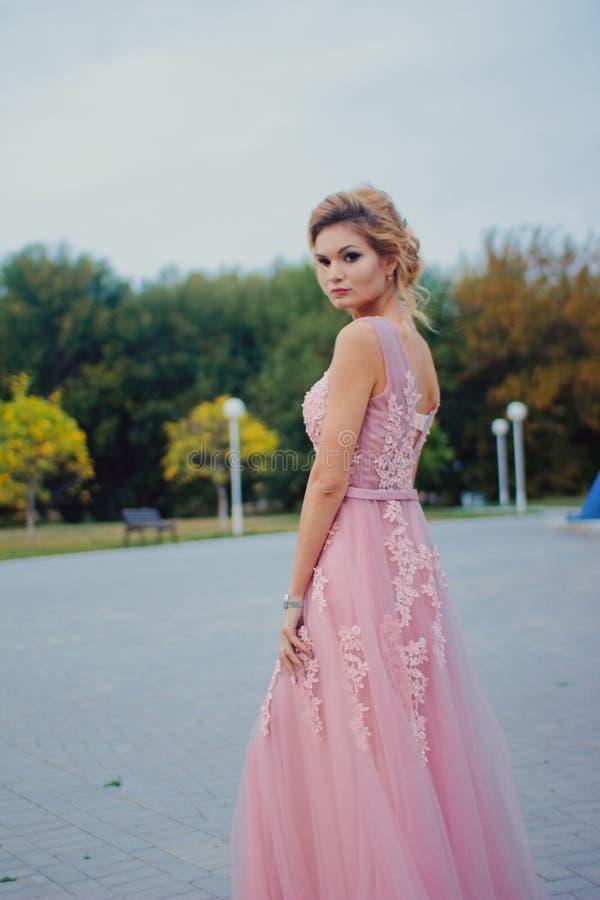 Mujer hermosa joven en trayectoria que camina rosada larga del vestido de noche en parque Forme el retrato del estilo de la mucha imagen de archivo libre de regalías