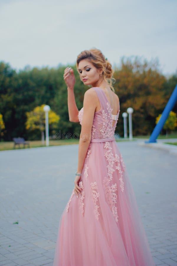 Mujer hermosa joven en trayectoria que camina rosada larga del vestido de noche en parque Forme el retrato del estilo de la mucha fotografía de archivo