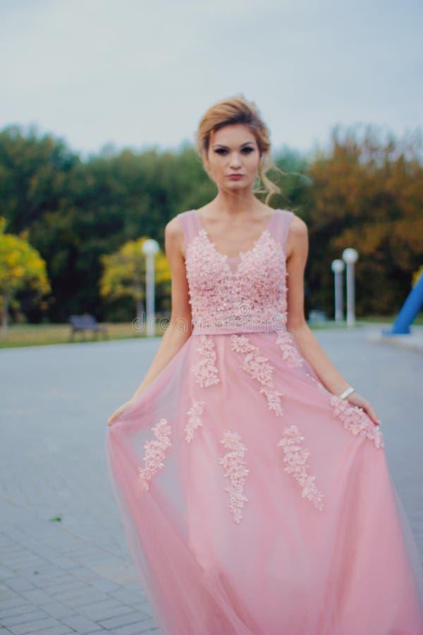 Mujer hermosa joven en trayectoria que camina rosada larga del vestido de noche en parque Forme el retrato del estilo de la mucha fotos de archivo