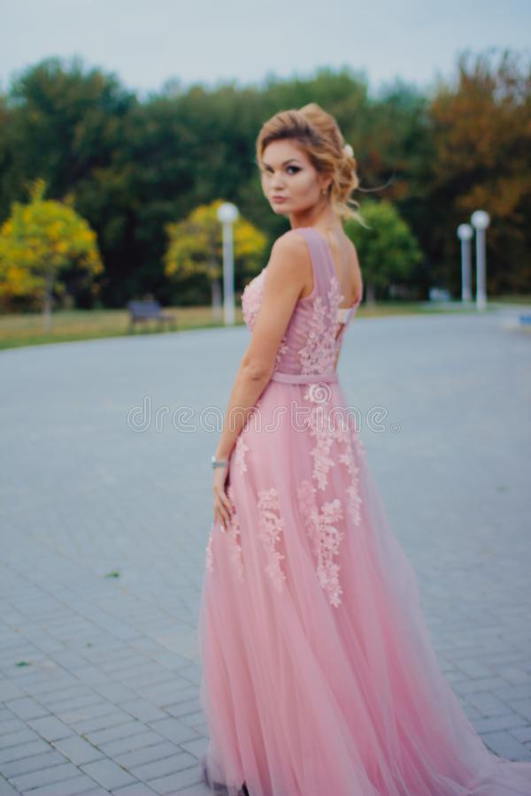 Mujer hermosa joven en trayectoria que camina rosada larga del vestido de noche en parque Forme el retrato del estilo de la mucha imagenes de archivo