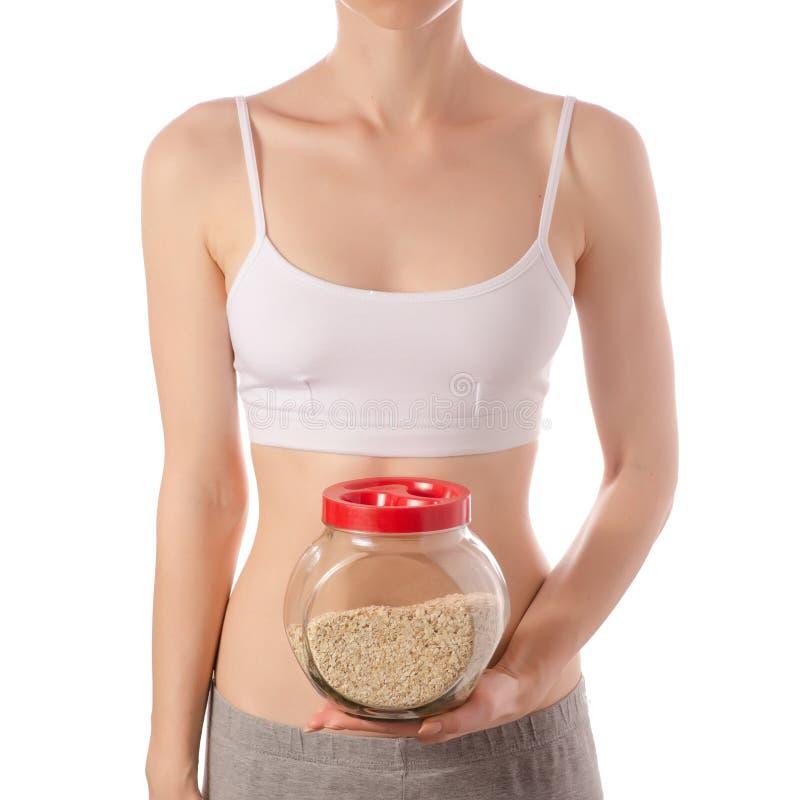 Mujer hermosa joven en un top blanco de la camiseta en el tarro del vidrio de manos de belleza de las gachas de avena de la harin fotos de archivo libres de regalías