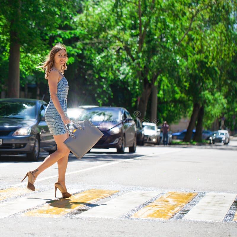 Mujer hermosa joven en un vestido corto azul que camina en el camino fotografía de archivo libre de regalías
