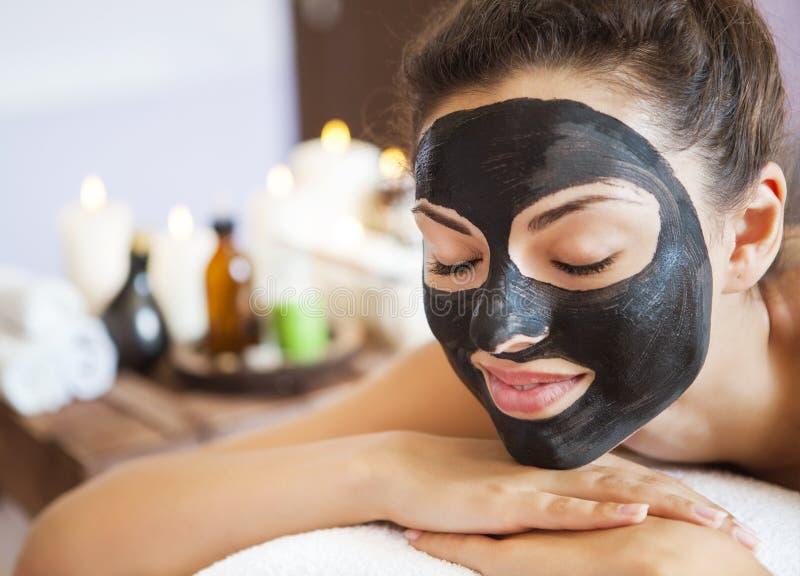 Mujer hermosa joven en una máscara para la cara del terapéutico fotos de archivo